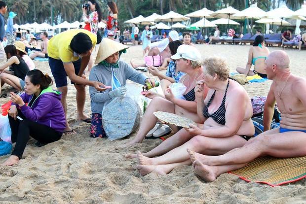 Du khách nước ngoài cũng đổ về biển để tắm mát. Trong ảnh, nhóm du khách nước ngoài đang ngồi nghỉ trên bãi biển, thưởng thức món bánh tráng nướng (ảnh: Vietnamnet)
