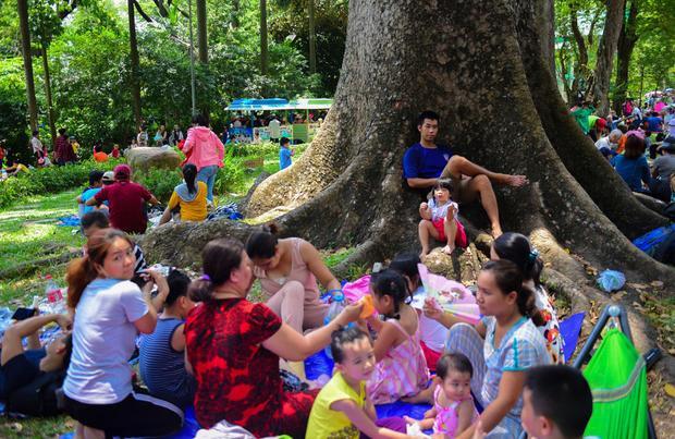 Nhiều gia đình từ các tỉnh thành lân cận đổ về đây mang theo những vật dụng như bạt, võng, đồ ăn… để tận hưởng kỳ nghỉ lễ tại sở thú lớn nhất Sài Gòn - Ảnh: Tuổi trẻ.