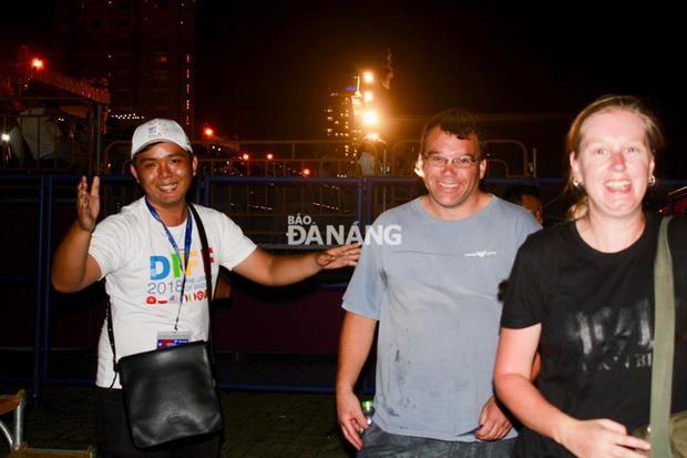 Một tình nguyện viên DIFF 2018 hướng dẫn du khách nước ngoài lên khán đài. Ảnh: baodanang.