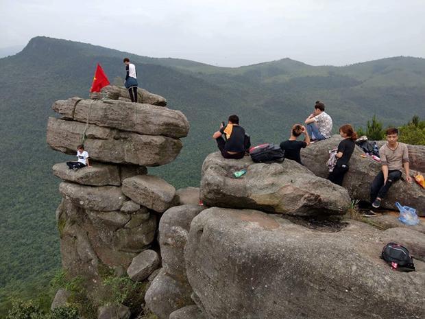 Các bạn trẻ leo lên mỏm đá chênh vênh ở Quảng Ninh để chụp ảnh. Ảnh: P.L/ Zing.vn