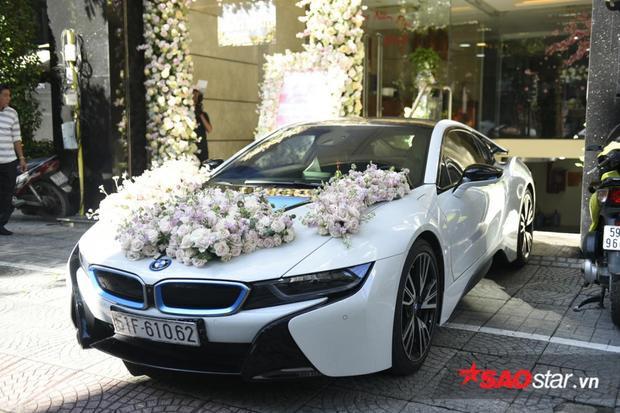 """""""Nhân vật"""" chính trong dàn xe đón dâu của nhà tra là một chiếc BMW i8 với hoa hồng được kết trên nắp capô cực kì ấn tượng và mang đậm phong cách một đám cưới truyền thống. Chiếc xe này được cho là có giá trên dưới 7 tỷ đồng."""
