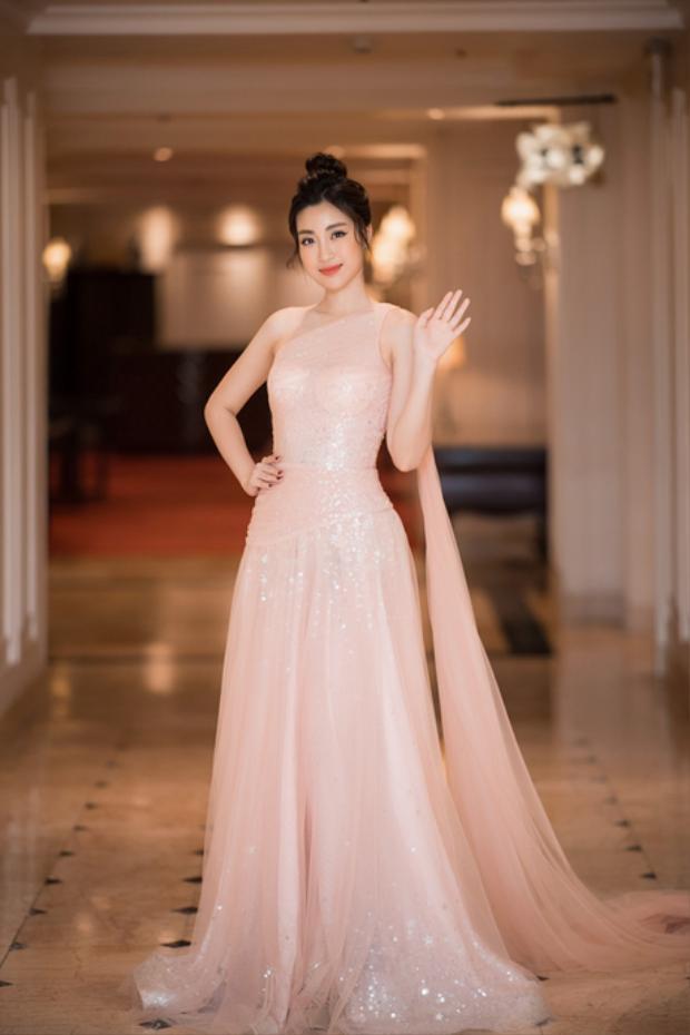 Đỗ Mỹ Linh xinh đẹp như nữ thần với chiếc đầm dài lệch vai chất liệu sequin lấp lánh. Kiểu tóc bới cao, để rũ lòa xòa vài cọng tóc mái khiến khuôn mặt trái xoan của đương kim Hoa hậu Việt Nam càng được tôn lên.