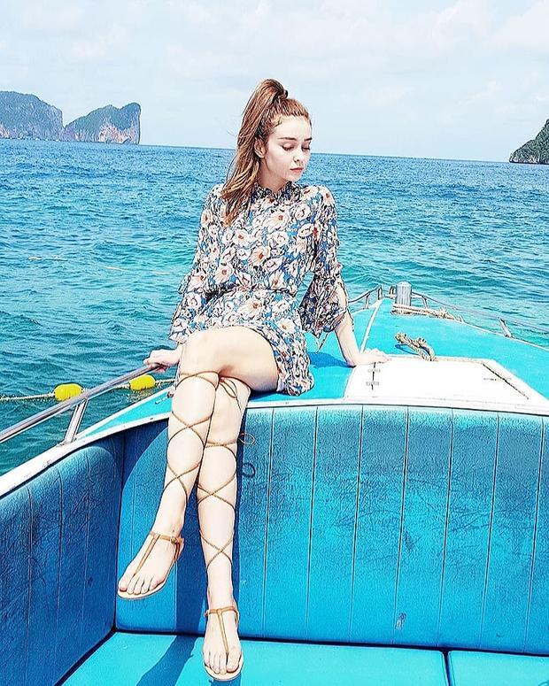 Chiếc váy ngắn in hoa phối cùng giày buộc dây là sự lựa chọn của Mlee khi tận hưởng chuyến du lịch trên thuyền vào ngày hè.