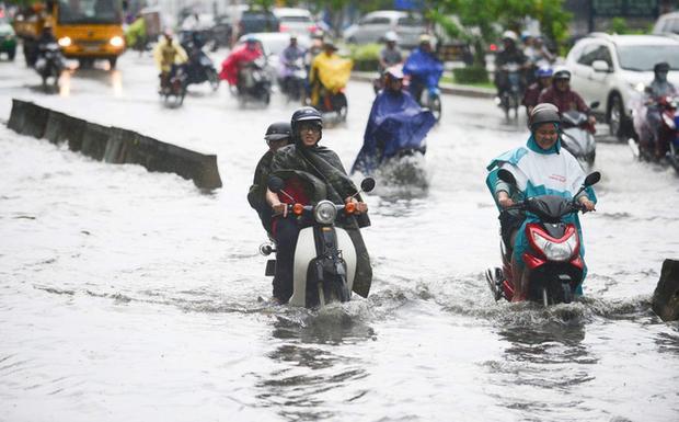 Người đi xe máy rất vất vả chạy qua đoạn đường ngập. Ảnh: Soha.
