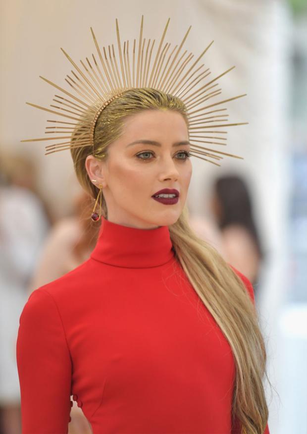 Amber Heard nổi bật trên thảm đỏ Met Gala với làn môi đỏ thẫm. Cô buộc tóc đuôi ngựa cao và 'đụng' ý tưởng phụ kiện tóc với nhiều mỹ nhân khác.