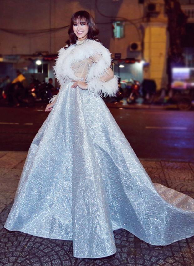 Khánh Myxuất hiện cầu kì, lộng lẫy khi diện một thiết kế tông màu xám bạc. Bộ trang phục kết hợp chất liệu ánh kim, lông vũ trông khá nặng nề. Nữ diễn viên phải nhờ một số người phụ giúp để có thể bước vào không gian buổi tiệc.
