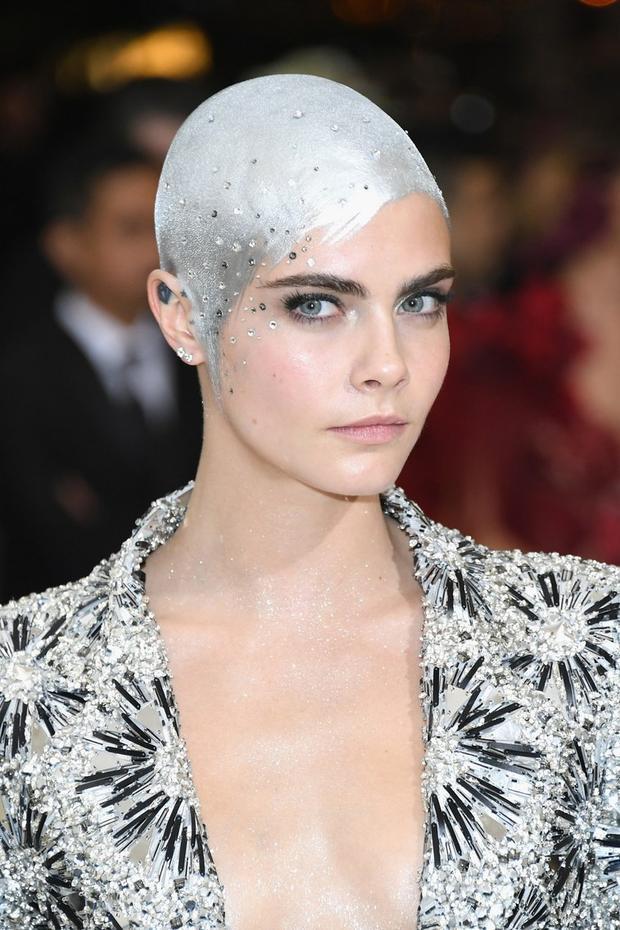"""Cara Delevingne có thể không phải là nhân vật sở hữu trang phục ấn tượng nhất tại Met Gala 2017 nhưng nếu xét về khoản trang điểm, hẳn toàn bộ dàn khách mời đều phải ngả mũ trước sự sáng tạo và """"chịu chơi"""" của cô nàng. Siêu mẫu nước Anh đã cạo trọc, phủ sơn màu bạc lên toàn bộ da đầu và đính đá trắng vô cùng ton-sur-ton với trang phục. Quả là một lựa chọn không thể tương hợp hơn với chủ đề thời trang trừu tượng của Met Gala năm ngoái."""