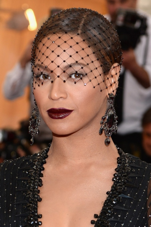 """Ở bất cứ nơi đâu mình xuất hiện, Beyonce cũng khẳng định ngôi vị """"nữ hoàng"""" và Met Gala 2014 cũng không ngoại lệ. Chủ đề năm đó là Charles James, NTK Haute Couture đầu tiên của nước Mỹ và Beyonce đã chọn kiểu makeup không thể quyền quý hơn: môi đỏ thẫm burgundy kết hợp mạng che mặt pha lê."""