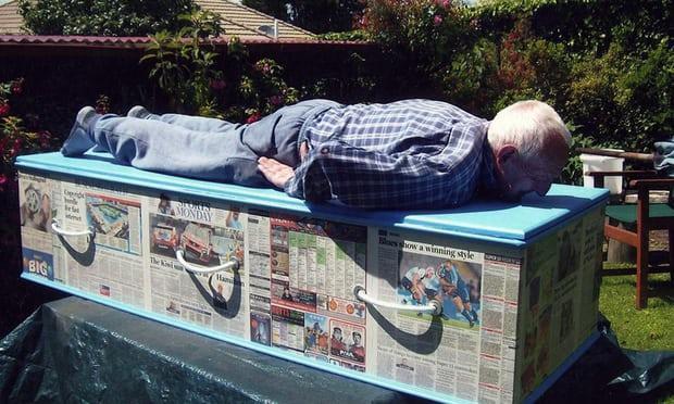 Một thành viên trong câu lạc bộ Kiwi nằm trên chiếc quan tài bọc giấy báo của chính ông.