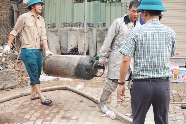 Lực lượng chức năng đưa nhiều bình gas ra ngoài.