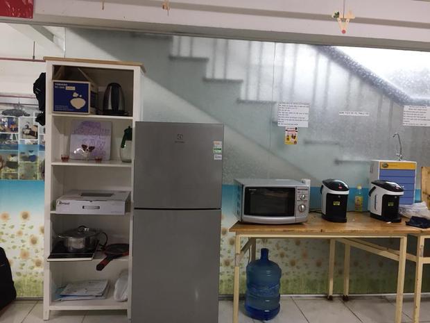 """Gian bếp nhỏ tại """"Góc chia sẻ"""" được trang bị tủ lạnh, bình nấu nước sôi, lò vi sóng để phục vụ pha mì tôm tại chỗ hoặc để hâm nóng thức ăn hoàn toàn miễn phí."""