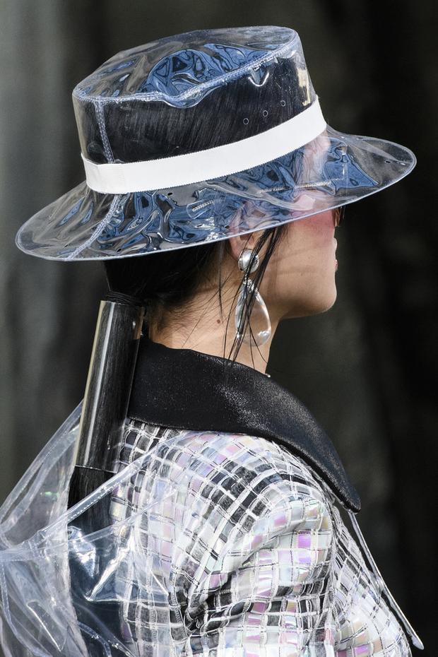 """Chanel là một trong những thương hiệu tích cực """"lăng xê"""" loạt phụ kiện trong suốt. Trong BST Xuân, Hè 2018, nhà mốt trình làng nhiều thiết kế từ nhựa PVC như boots, túi xách, găng tay, mũ… Đơn cử như kiểu mũ rộng vành có giá bán gần 27 triệu đồng."""