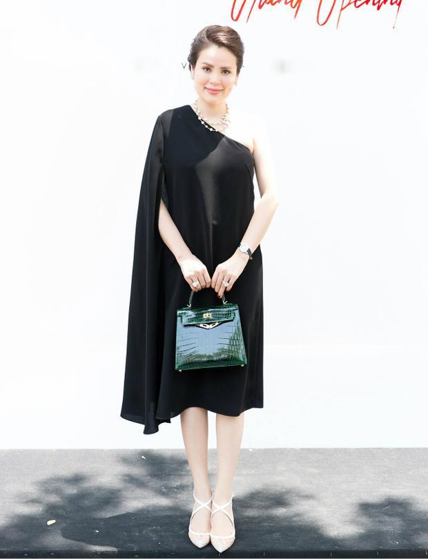 Hoa hậu Quý bà - Phương Lê trẻ trung với thiết kế lệch vai, phom rộng. Cô kết hợp trang phục cùng giày cao gót đan chéo thanh mảnh, đồng hồ, hoa tai có kích thước tương xứng với trang phục, chiếc túi Hermes màu xanh ngọc sang trọng.