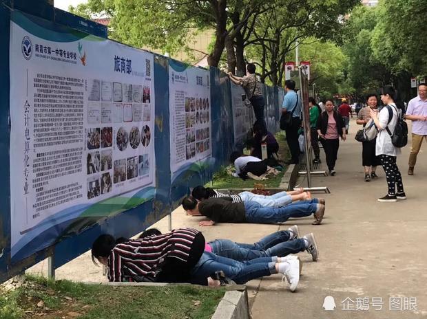 Hình ảnh phụ huynh nằm rạp xuống đất để cố nhìn con thi đại học qua các khoảng hở đang dấy lên tranh luận trái chiều trên mạng xã hội Trung Quốc.