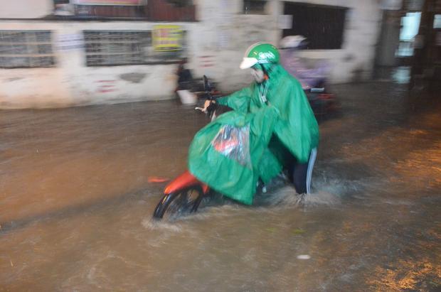 Hình ảnh người dân phải cùng xe lội nước ở phố Chính Kinh. Ảnh: Định Nguyễn.