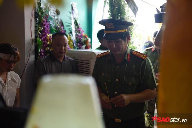 Một chiến sĩ công an thắp nén hương trước linh cữu của anh Nam.