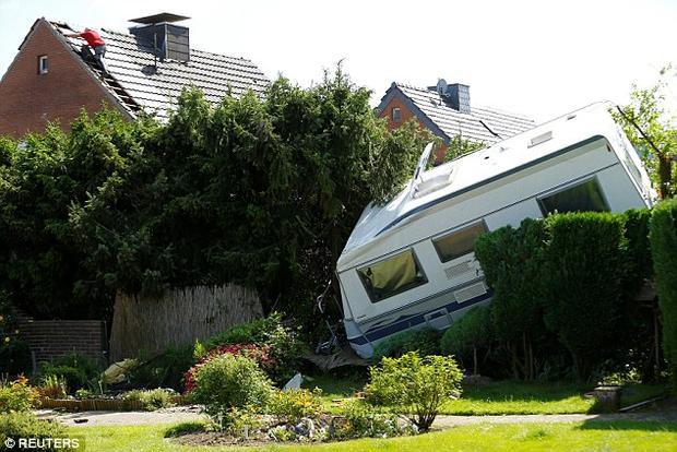 Một khu vườn bị phá hủy, hàng chục chiếc xe bị thổi tung.