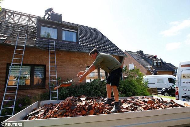 Người dân đang dọn dẹp sau khi cơn lốc xoáy đi qua.
