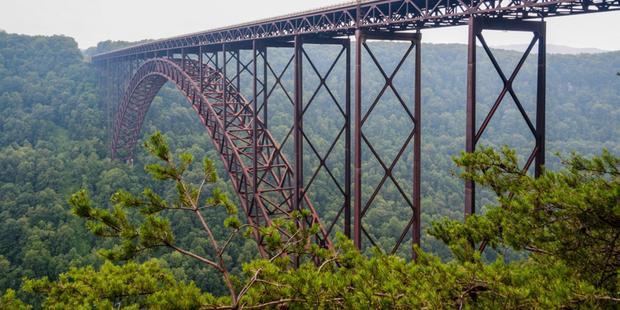 """New River Gorge Bridge xây dựng xong vào năm 1977 và nó được thiết kế để giải quyết vấn đề đi lại khó khăn. Trước khi cây cầu này được xây dựng, du khách đã phải đi 40 phút lái xe dọc theo một dòng sông cũ và những con đường núi hẹp, nhưng cây cầu giờ đây cho phép họ di chuyển cùng đoạn đường chỉ với 1 phút lái xe.Do vị trí tuyệt đẹp của nó, cây cầu này đã trở thành một trong những nơi được chụp ảnh nhiều nhất. Thế nhưng, nhiều người nó rằng khi di chuyển trên cây cầu này mang lại cảm giác rùng mình vì có cảm giác những chiếc lan can hai bên dường như """"mất hút"""" giữa khung cảnh hùng vĩ hai bên."""