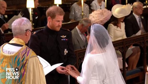 """Hoàng tử Harry trao nhẫn cho Meghan.Giám mục Canterbury chủ trì lễ đọc lời thề nguyện. Sau khi Harry và Meghan đọc lời thề, Giám mục Canterbury nói: """"Ta tuyên bố hai con là vợ chồng""""."""