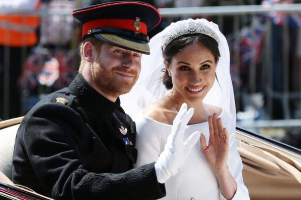 Hoàng tử Harry và Meghan Markle vẫy tay chào người dân trong lễ diễu hành bằng xe ngựa quanh Windsor. Ảnh: Getty