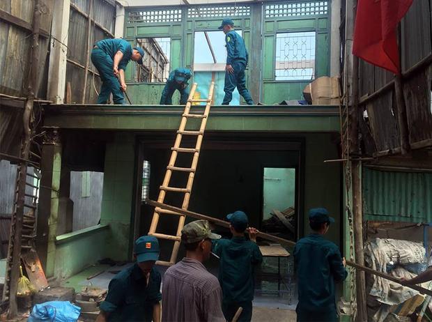 Lực lượng chức năng giúp người dân thu dọn tài sản ra khỏi vùng sạt lở.