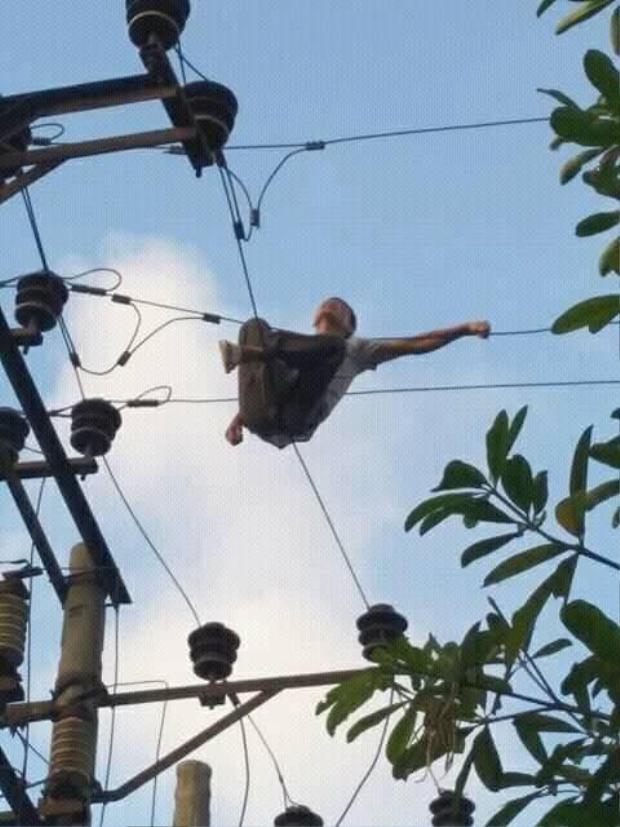 Người đàn ông ngồi vắt vẻo trên cây. Ảnh: Thế giới trẻ.