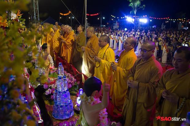 Các vị sư đứng trước tượng Phật làm lễ.
