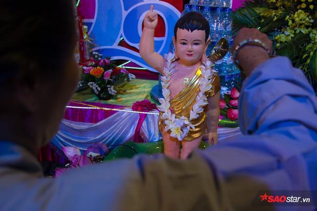 Dòng nước mát được mọi người cẩn thận dội lên mình tượng Phật.
