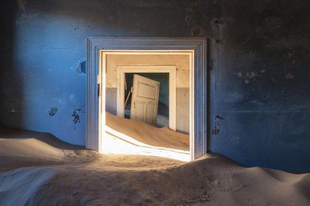 """Khu mỏ kim cương ở Kolmanskop, Namibia được phát hiện vào năm 1908 bởi những người định cư gốc Đức. Thị trấn đã trải qua một """"cơn sốt kim cương"""" và nhanh chóng trở thành trung tâm đầu não trong khu vực. Vào năm 1954, thị trấn bị bỏ hoang hoàn toàn. Kể từ đó, thị trấn bị chôn vùi bởi cát của sa mạc Namabia. Ngày nay, chỉ khách du lịch ghé thăm Kolmanskop."""