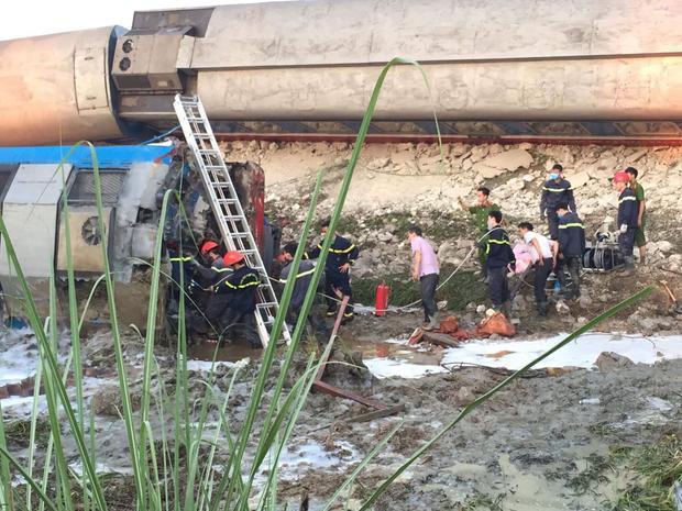 Lực lượng cứu hộ đang khẩn trương cẩu các toa tàu bị lật.