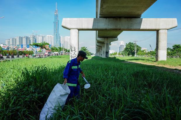 Công nhân môi trường thu gom rác trong hành lang tuyến metro, đoạn gần cầu Sài Gòn.