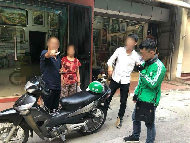 Người đàn ông (mặc áo đen) vô cớ hành hung tài xế Grab Bike và lớn tiếng chửi bới, chỉ tay hăm dọa vị khách của tài xế này. Ảnh: Joog Nguyen.