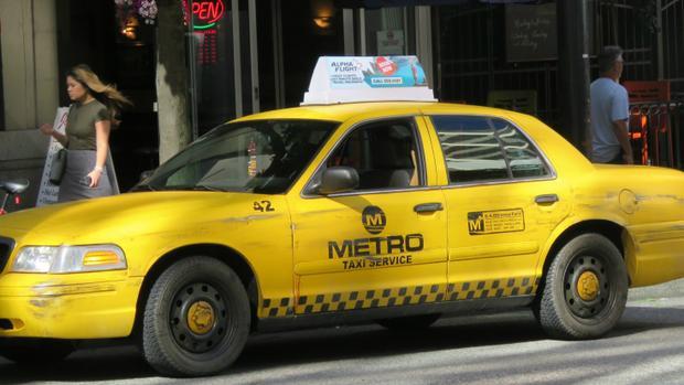 """Chiếc xe taxi của Dopinder với biển quảng cáo hãng hàng không """"Alpha Flight"""" trên nóc."""