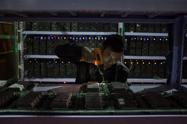 Một nhân viên đang lắp ráp một bảng mạch tính toán. Đào bitcoin được nhiều người ví như một cuộc đua.