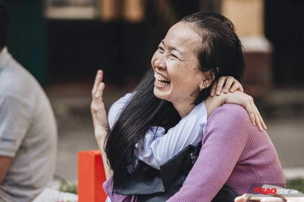 Hai mẹ con đan tay vào nhau, ngồi lặng lẽ sau sân trường lắng nghe buổi lễ.