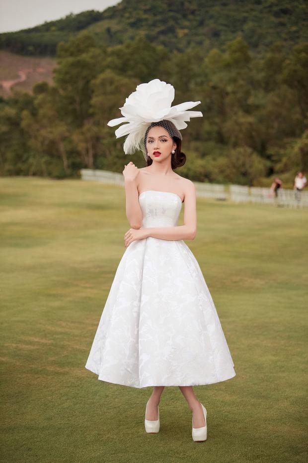 Hoa hậu Hương Giang Idol nổi bật với trang phục tông trắng khi kết hợp cùng phụ kiện hoa đội đầu to bản.