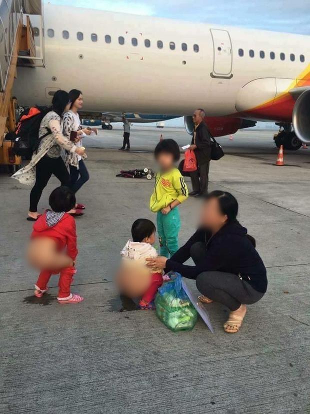 Người phụ nữ cho 2 bé gái đi vệ sinh giữa đường băng sân bay.