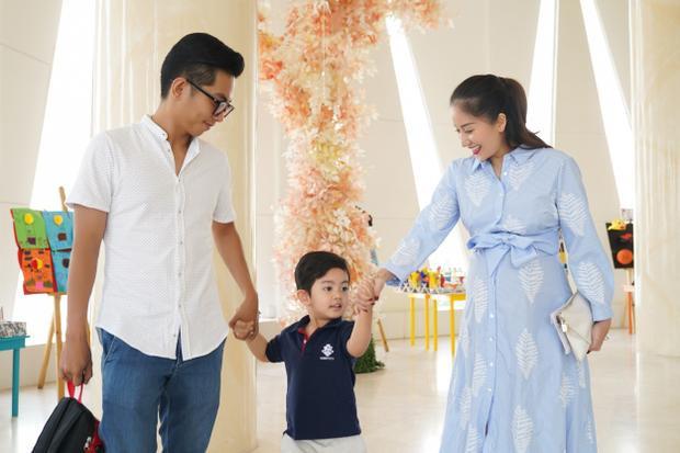 Kubi vui vẻ nắm tay bố mẹ đến dự lễ.