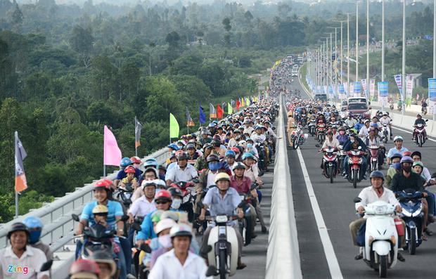 Tại dốc lên hai bên cầu, làn đường dành cho xe máy kín đặc. Lực lượng chức năng mở thêm làn phần ôtô để giải phóng tình trạng ùn tắc cục bộ.
