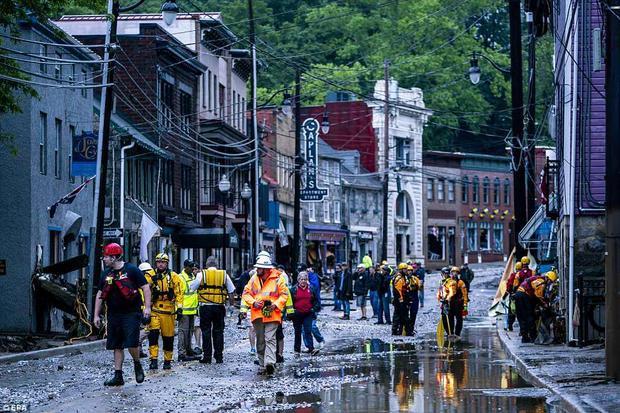 Nhân viên cứu hộ kiểm tra thiệt hại trên đường sau trận lũ quét lịch sử tràn qua thành phố. Hiện vẫn chưa có thống kê về thương vong về trận lũ quét này.