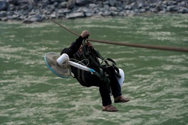 Một người đàn ông mang theo quạt, treo lơ lửng trên dây đu giữa dòng sông dữ.