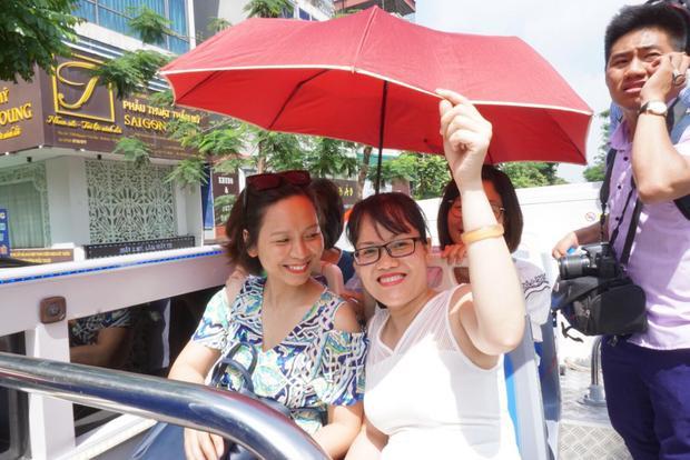 Dù thời tiết sáng 30/5 khá oi nóng nhưng nhiều hành khách khá thích thú. Họ sẵn sàng che ô, đội mũ.. để ngắm phố phường Hà Nội.