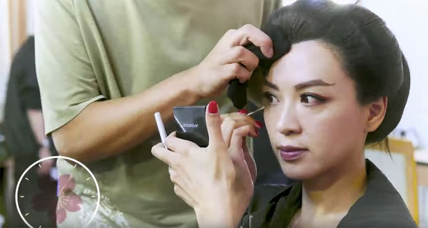 Nhân lúc thợ trang điểm đang tạo hình tóc giả, Trần Vỹ lợi dụng thời gian rảnh tự mình hóa trang.