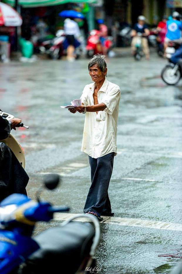 Cả một buổi cụ ông tay mời mua vé số, miệng khóc, chân rảo bước dưới cơn mưa.