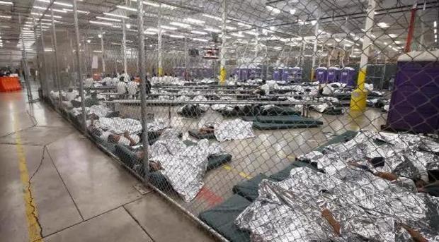 Hình ảnh ghi lại cảnh hàng trăm đứa trẻ phải ngủ và xem tv trong một chiếc lồng sắt lớn hơn - nơi mà rất nhiều trẻ nhập cư tại vùng Trung Mỹ đang chờ được điều tra. Ảnh: AP