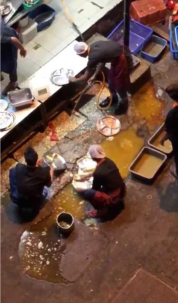 Các nhân viên nhà hàng rửa bát đĩa ngay trong vũng nước bên đường.