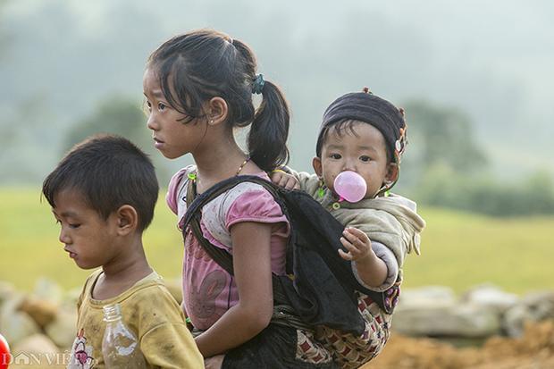 Một em nhỏ thổi bong bóng từ kẹo cao su xuống chợ cùng chị gái.