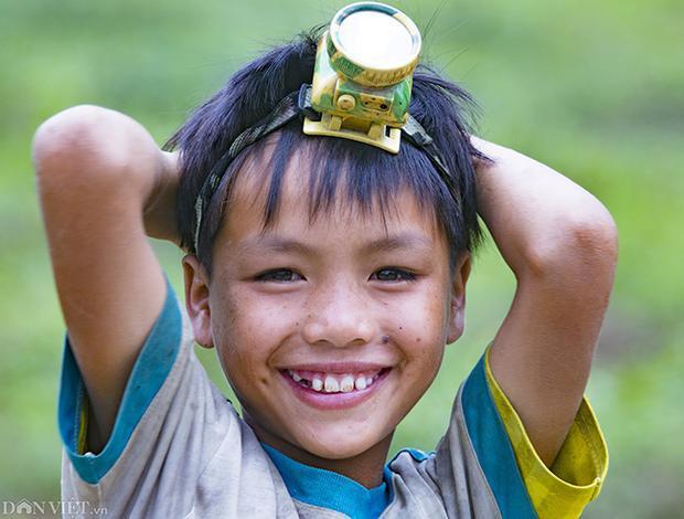 Nét hồn nhiên của một em nhỏ, phía trên đầu em là một chiếc đèn pin sạc bằng điện. Chiếc đèn pin dùng để soi đường, hay đi bắt những chú ếch, cóc vào buổi tối.