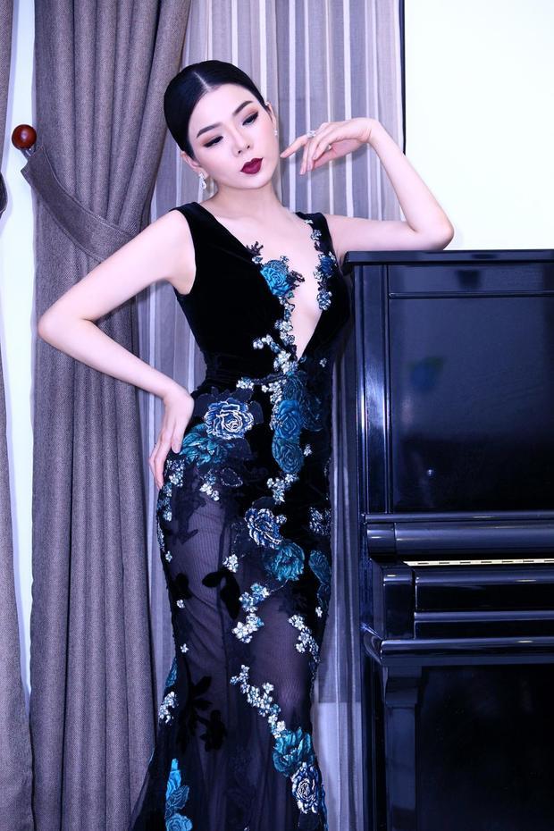 """Trong thiết kế của """"ông hoàng váy dạ hội"""" có tông màu chủ đạo là đen và điểm những bông hoa màu xanh vô cùng tinh tế và sang trọng, Lệ Quyên như một """"nữ hoàng"""" quyền lực và bí ẩn. Chiếc váy được cắt may khéo léo làm tôn lên vóc dáng đồng hồ cát đầy gợi cảm của nữ ca sĩ."""